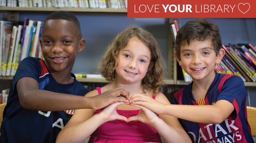 Three children form a heart shape with their hands in the library, with a Love Your Library logo.