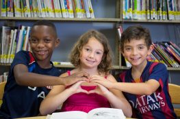 Three children form a heart shape with their hands in the library