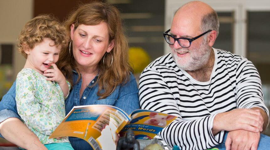 Parents read at the Library with their two-year-old daughter.