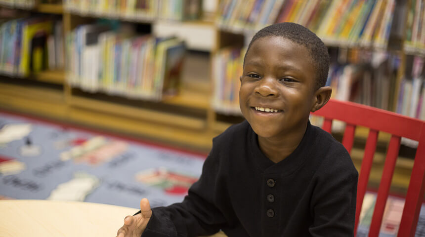 child sitting and smiling in the library