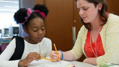 woman helping girl with homework