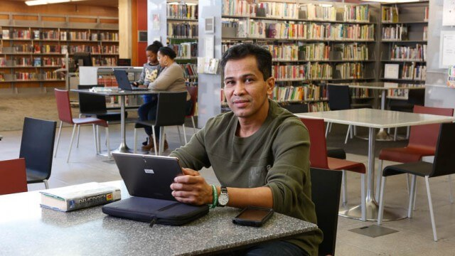 Person posing with tablet among book shelves at CLP-Squirrel Hill