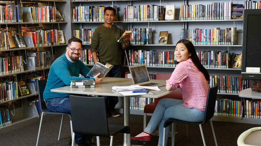 Three people posing with books and laptop among book shelves at CLP-Squirrel Hill