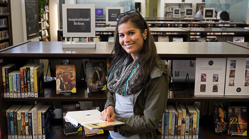 woman holding book and smiling