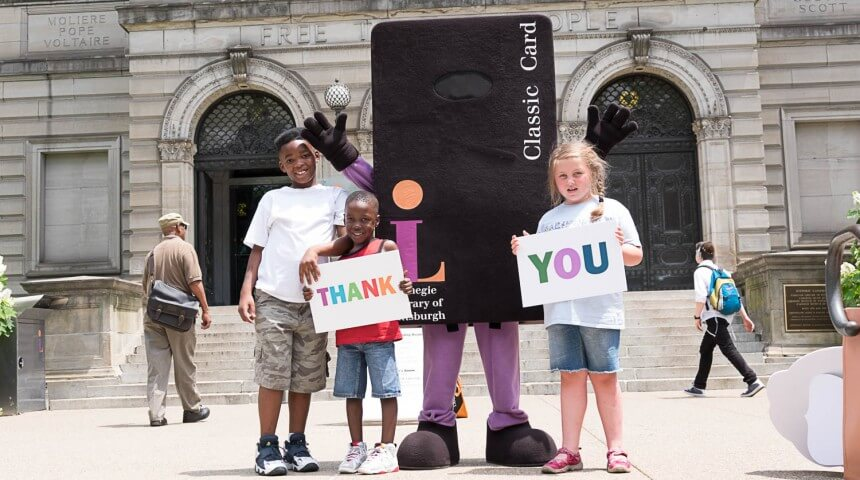 Three children stand in front of the library with Library mascot Andrew Cardnegie while holding thank you signs