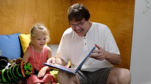 adult and child reading and laughing