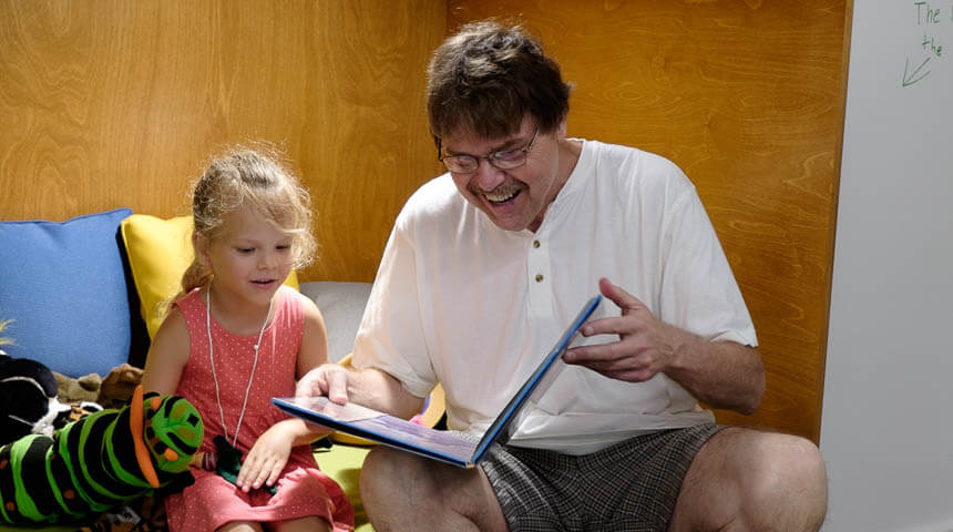 man and child reading and laughing