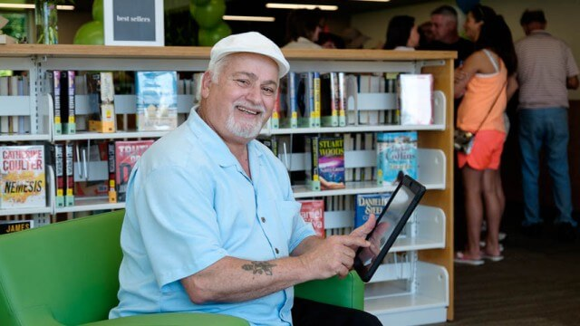 older man smiling with tablet in the library