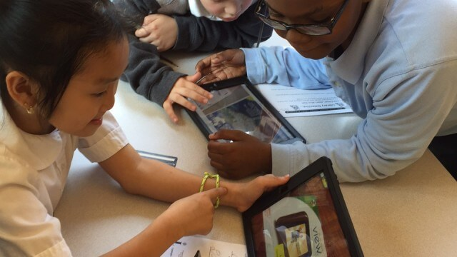 Three children gather around a digital tablet for a group project