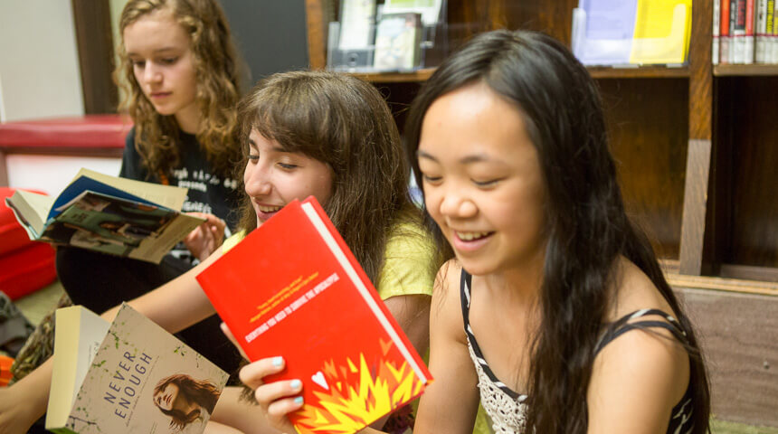teen girls smiling and looking at books