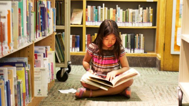 Child sitting cross legged on the floor in the stacks at the library with a book on their lap