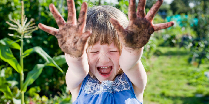 A young girl playing in the garden with mud-covered hands.