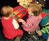 Two babies explore a xylophone held by a caregiver during Little Learners Playtime program