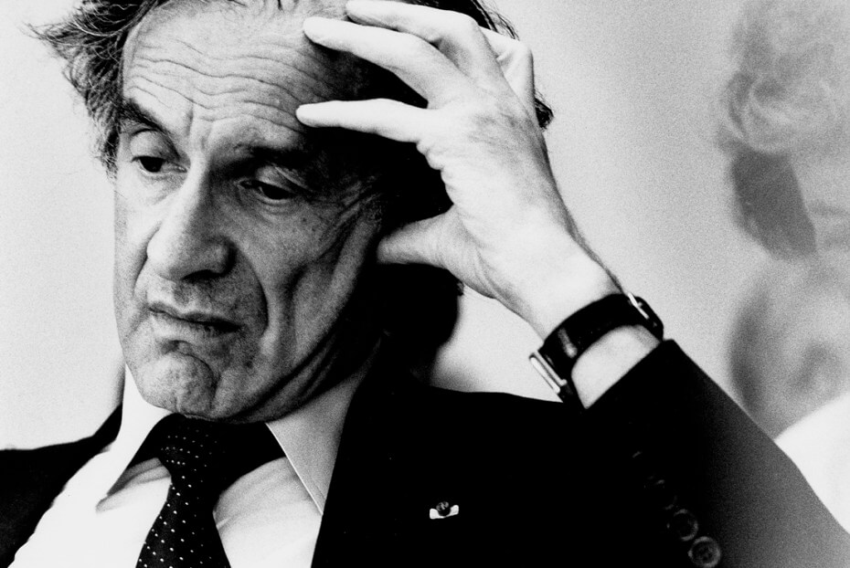Black and white photograph of Elie Wiesel with his hand resting on the side of his head, eyes cast down as if in thought.