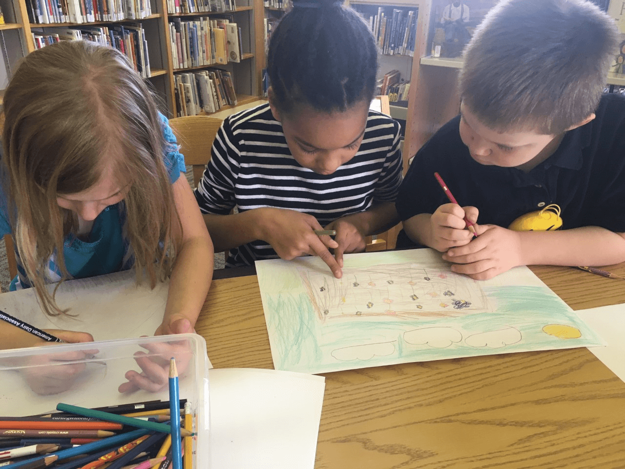 Three homeschool students draw with colored pencils togeher at CLP - Main.