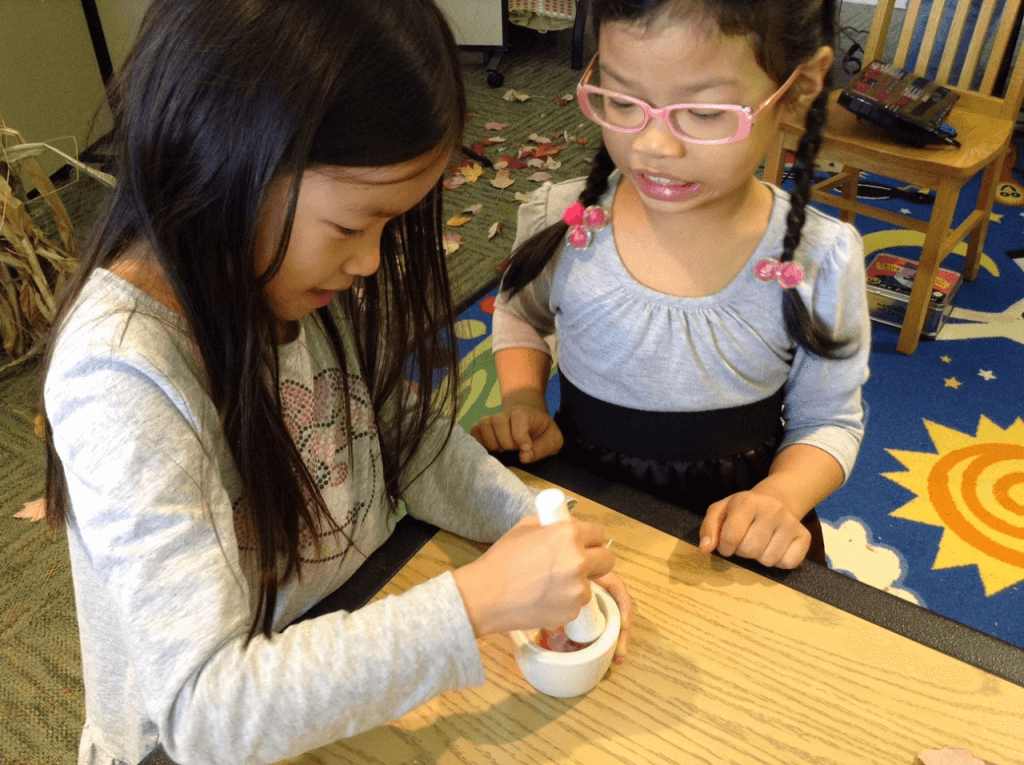 Homeschool students use a mortar and pestle during a library program.