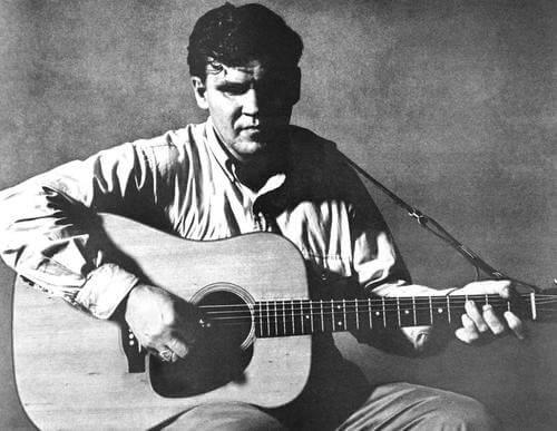 Doc Watson playing a guitar