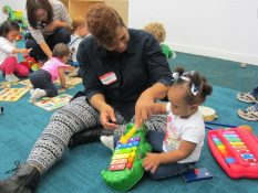 A caregiver helps a young toddler play with a xylophone