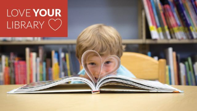 Child looking through a heart made from the pages of an open book