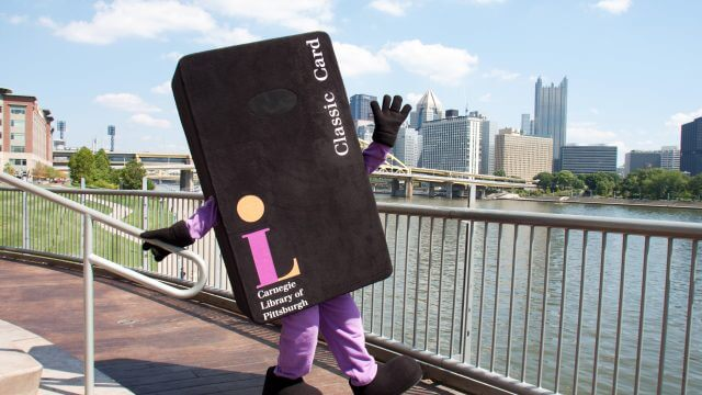 CLP mascot Andrew Card Negie posing in front of downtown Pittsburgh skyline