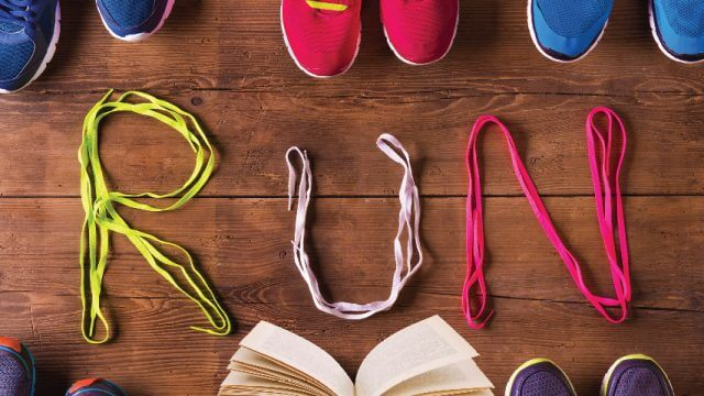 "Running shoes and a book with shoelaces that spell out ""RUN"""