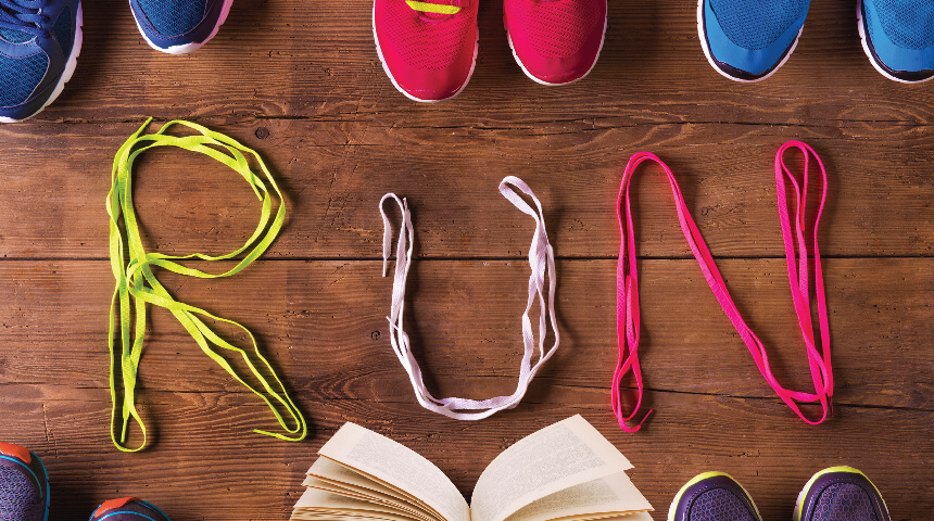 """Running shoes and a book with shoelaces that spell out """"RUN"""""""