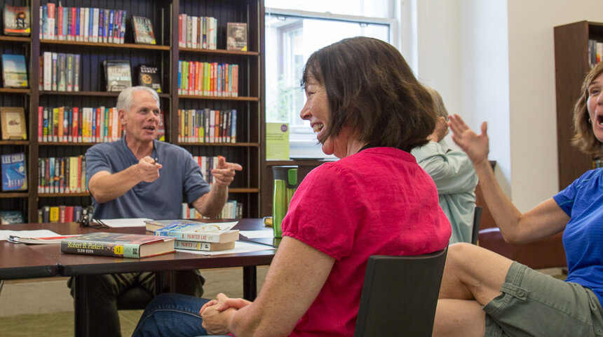 A librarian and adult participants seated at a table having a book club discussion.