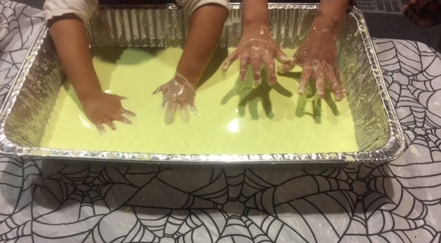 Children dipping their hands in the green goo, a mixture of cornstarch, water and food coloring