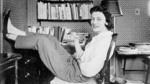 Anne Sexton sitting in front of a bookcase