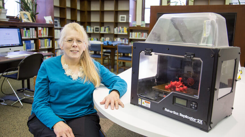 Cheryl next to a 3-D printer in the Library