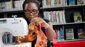 teenage girl using a sewing machine in the Library