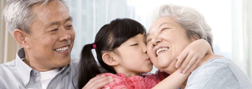 A young girl hugs and kisses her grandma as her grandpa looks at them and smiles.