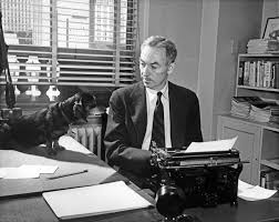 Photo of E.B. White and a dog sitting at a desk in front of a typewriter