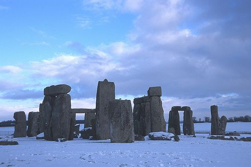 Stonehenge in winter, snow on the ground, the stones standing tall, with large lintel stones over the tops