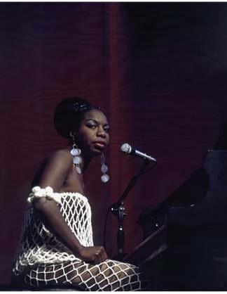 A photograph of Nina Simone sitting at a piano.