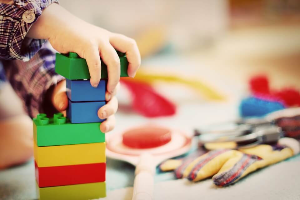 Photograph of young child's hands stacking blue, green, yellow, and red Legos with more toys in the background.