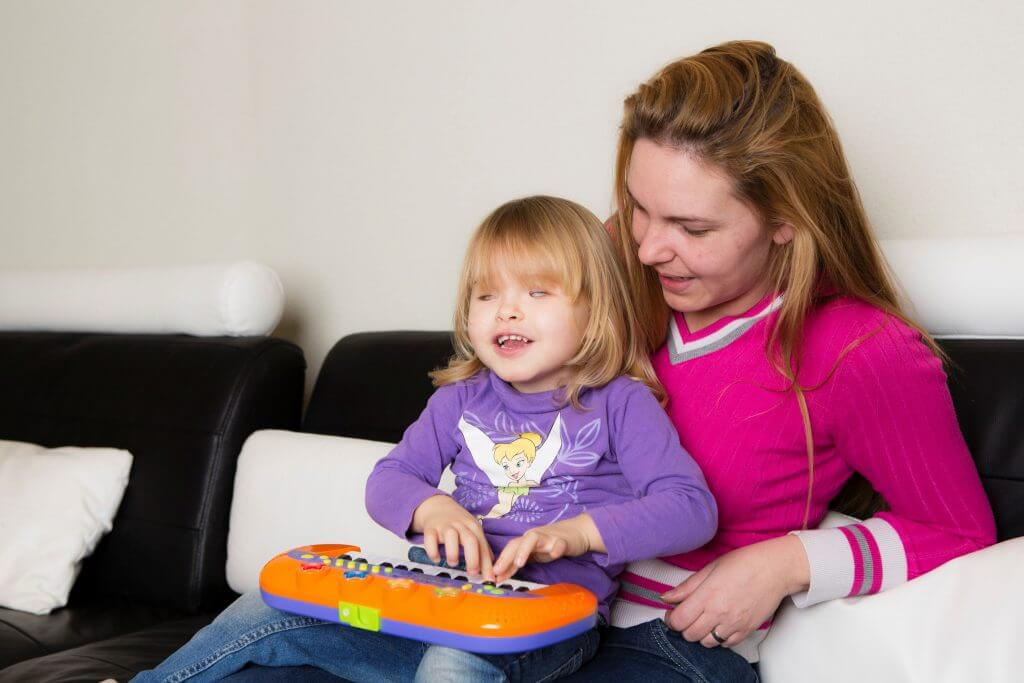 Child with a visual impairment sits on caretaker's lap while playing with a toy piano and smiling.