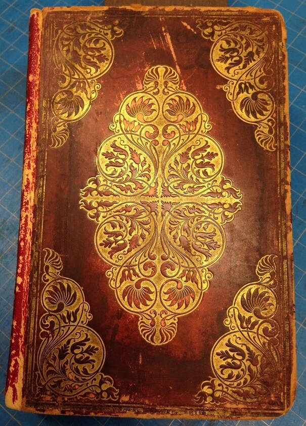 Photo of an old book with a red leather cover and gold accents.