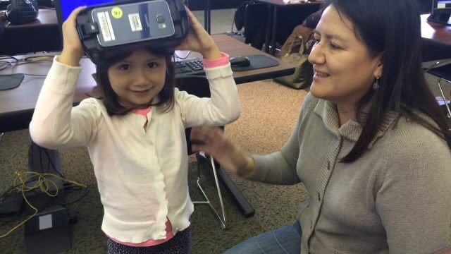 A little girl trying on CLP's VR equipment.