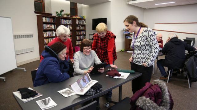 group of people gather around a table looking at tablet