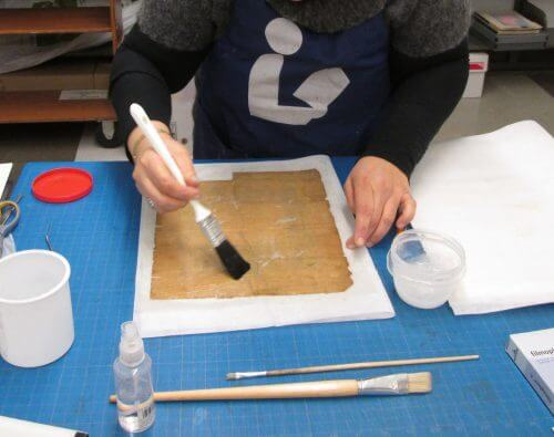 A photo of a preservationist working on a manuscript.