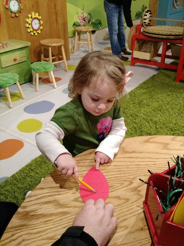 A toddler develops fine motor skills by drawing with a pencil.
