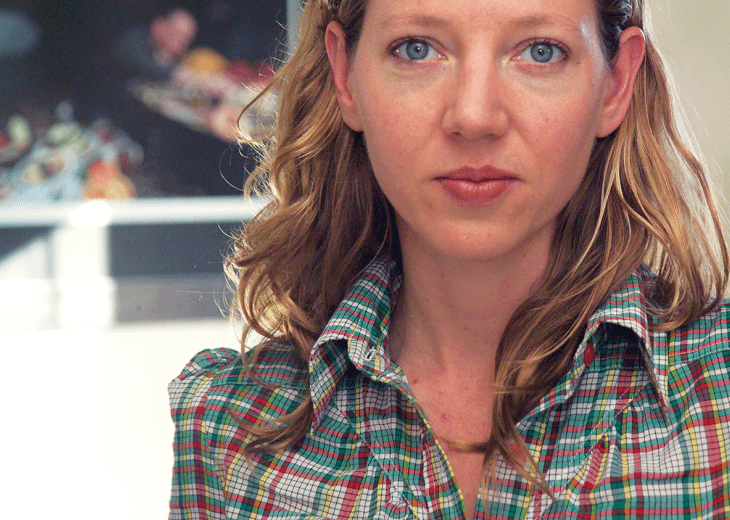 Photo of author Maggie Nelson in a plaid shirt, starring straight at the camera