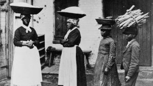 Black women in the reconstruction era South carrying dry goods on their heads with large baskets.