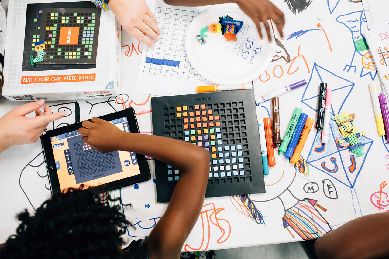 Overhead shot of children playing with iPads and the Bloxels design kit.