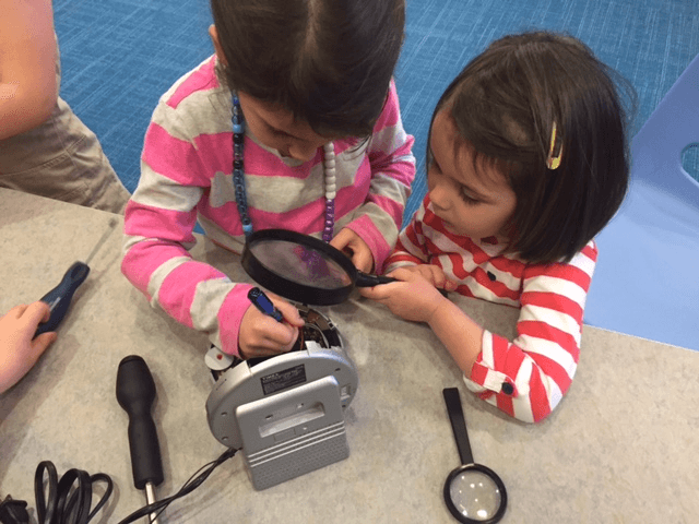 Sisters, Lucy and Hannah, explore the inside of a clock.