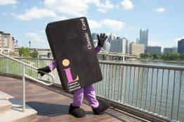 CLP mascot Andrew Card Negie poses in front of view of Pittsburgh skyline.