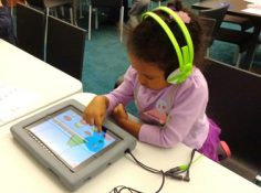 Young girl plays a game on an iPad.