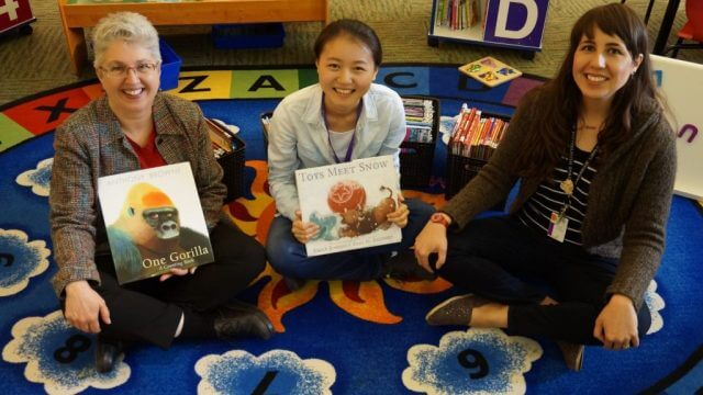Dutian, A Chinese language volunteer, sits with Lisa and Bonny