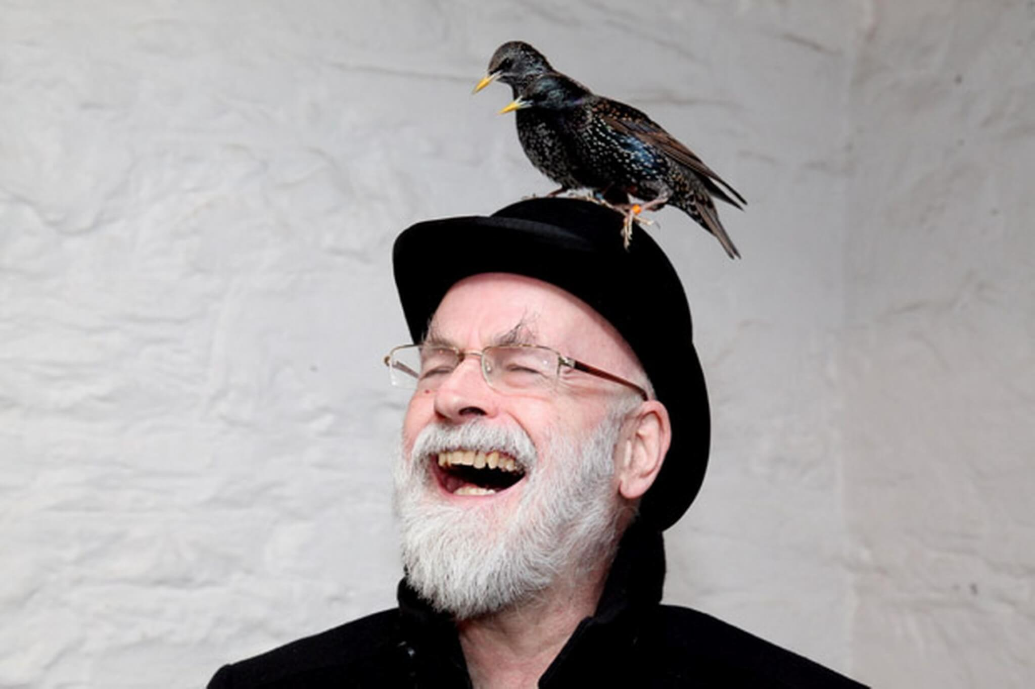 Terry Pratchett, laughing, wearing a derby hat with 2 birds perched on his head.